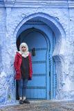 Μια γυναίκα μπροστά από μια χαρακτηριστική μαροκινή πόρτα, Chefchaouen Μαρόκο Στοκ Φωτογραφία
