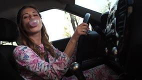 Μια γυναίκα οδηγεί ένα αυτοκίνητο, μασά μια τσίχλα και διογκώνει ένα μπαλόνι στην αίθουσα r απόθεμα βίντεο