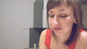 Μια γυναίκα πίνει το οινόπνευμα και χαμογελά στην αμηχανία φιλμ μικρού μήκους
