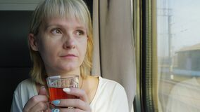 Μια γυναίκα πίνει το τσάι στο τραίνο Ταξίδι με την άνεση απόθεμα βίντεο