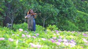 Μια γυναίκα παίζει το βιολί στην παραλία κοντά στον τομέα λουλουδιών απόθεμα βίντεο
