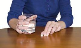 Μια γυναίκα παίρνει ένα χάπι Στοκ εικόνες με δικαίωμα ελεύθερης χρήσης