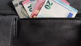 Μια γυναίκα παίρνει έξω έναν ευρο- λογαριασμό από τη μαύρη τσάντα δέρματος γοητείας της απόθεμα βίντεο