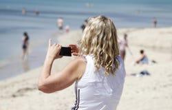 Μια γυναίκα παίρνει μια εικόνα με το κύτταρό της Arenal στην παραλία Στοκ Εικόνες
