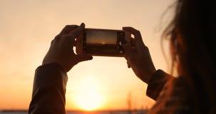 Μια γυναίκα παίρνει τις εικόνες ενός ηλιοβασιλέματος σε ένα smartphone απόθεμα βίντεο