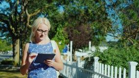 Μια γυναίκα περπατά κάτω από την οδό μιας μικρής αμερικανικής πόλης, εξετάζει τον τρόπο στην ταμπλέτα απόθεμα βίντεο