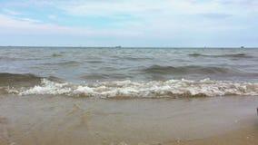 Μια γυναίκα περπατά κατά μήκος της ακτής, και τα κύματα χαϊδεύουν τα πόδια της απόθεμα βίντεο