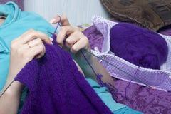 Μια γυναίκα πλέκει το πλέξιμο, στο κρεβάτι Ένα προϊόν φιαγμένο από σειρά της πορφύρας Στοκ εικόνα με δικαίωμα ελεύθερης χρήσης