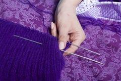 Μια γυναίκα πλέκει το πλέξιμο, στο κρεβάτι Ένα προϊόν φιαγμένο από σειρά της πορφύρας Στοκ φωτογραφία με δικαίωμα ελεύθερης χρήσης