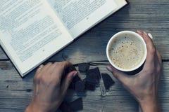 Μια γυναίκα που διαβάζει ένα βιβλίο πίνει τον καφέ Σοκολάτα στα χέρια των γυναικών Στοκ Εικόνες