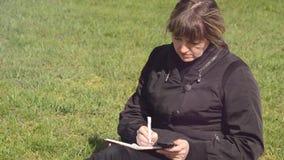 Μια γυναίκα που κοιτάζει στο τηλέφωνο και γράφει στο σημειωματάριο φιλμ μικρού μήκους