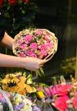 Μια γυναίκα που κρατά μια ανθοδέσμη των τριαντάφυλλων που τυλίγονται στο έγγραφο Στοκ φωτογραφία με δικαίωμα ελεύθερης χρήσης