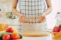 Μια γυναίκα που κρατά την ξύλινη ΑΓΑΠΗ επιστολών μαγειρεύοντας στην κουζίνα Στοκ Φωτογραφίες