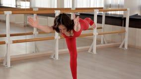 Μια γυναίκα που ντύνεται κόκκινο ελαστικό sportswear συμμετέχει σε Pilates σε ένα φωτεινό στούντιο με τους μεγάλους καθρέφτες r φιλμ μικρού μήκους