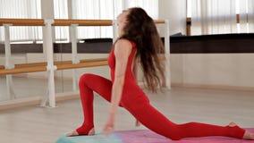Μια γυναίκα που ντύνεται κόκκινο ελαστικό sportswear συμμετέχει σε Pilates σε ένα φωτεινό στούντιο με τους μεγάλους καθρέφτες r απόθεμα βίντεο