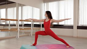 Μια γυναίκα που ντύνεται κόκκινο ελαστικό sportswear συμμετέχει σε Pilates στο στούντιο με τους μεγάλους καθρέφτες και τα παράθυρ απόθεμα βίντεο