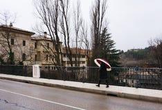 Μια γυναίκα που περπατά από τη γέφυρα στη μικρή πόλη στοκ φωτογραφία