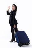 Μια γυναίκα που τραβά αποσκευές και που κυματίζει το χέρι Στοκ φωτογραφία με δικαίωμα ελεύθερης χρήσης