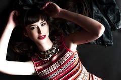 Μια γυναίκα που φορά ένα σακάκι δέρματος και ένα κόκκινο φόρεμα στοκ εικόνα με δικαίωμα ελεύθερης χρήσης