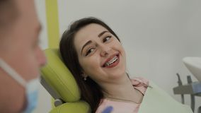 Μια γυναίκα που χαμογελά στην εργασία οδοντιάτρων του οδοντιάτρου με τον ασθενή Το τέλειο χαμόγελο απόθεμα βίντεο