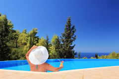 Μια γυναίκα που χαλαρώνει σε μια πισίνα με το κοκτέιλ στοκ φωτογραφία