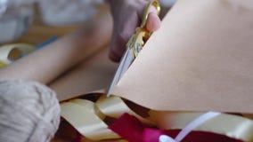 Μια γυναίκα, που χρησιμοποιεί το ψαλίδι, κόβει το έγγραφο για να τυλίξει ένα δώρο για έναν γάμο, τα γενέθλια, τα Χριστούγεννα, Πά απόθεμα βίντεο