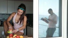 Μια γυναίκα προετοιμάζει το πρόγευμα για τον άνδρα της στην κουζίνα των φρούτων φιλμ μικρού μήκους