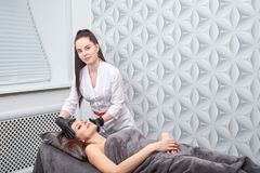 Μια γυναίκα προετοιμάζεται για μια διαδικασία αφαίρεσης τρίχας με ένα photoepilator στο σαλόνι στοκ φωτογραφία με δικαίωμα ελεύθερης χρήσης