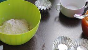 Μια γυναίκα προσθέτει το αλεύρι και τη ζάχαρη σε ένα εμπορευματοκιβώτιο του λειωμένου βουτύρου Αρχίστε να ζυμώνετε τη ζύμη για το φιλμ μικρού μήκους