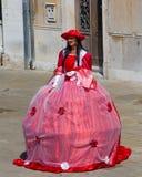 Μια γυναίκα προσκαλώντας ανθρώπους στους κόκκινους φορεμάτων για να την φωτογραφίσει σε ένα ST Στοκ Εικόνες