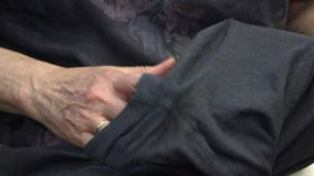 Μια γυναίκα ράβει τα ενδύματα με μια βελόνα φιλμ μικρού μήκους