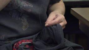 Μια γυναίκα ράβει τα ενδύματα με μια βελόνα απόθεμα βίντεο