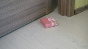 Μια γυναίκα ρίχνει ένα δώρο κάτω από την πόρτα φιλμ μικρού μήκους