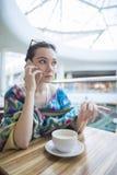 Μια γυναίκα σε έναν καφέ μιλά στο τηλέφωνο Στοκ φωτογραφία με δικαίωμα ελεύθερης χρήσης