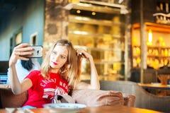 Μια γυναίκα σε έναν καφέ σε έναν πίνακα selfie στο τηλέφωνο Ένας επισκέπτης στο εστιατόριο παίρνει τις εικόνες του στο τηλέφωνο Γ Στοκ Φωτογραφία