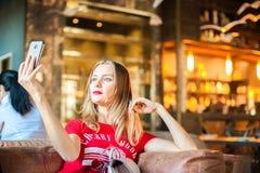 Μια γυναίκα σε έναν καφέ σε έναν πίνακα selfie στο τηλέφωνο Ένας επισκέπτης στο εστιατόριο παίρνει τις εικόνες του στο τηλέφωνο Γ Στοκ φωτογραφία με δικαίωμα ελεύθερης χρήσης