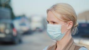 Μια γυναίκα σε έναν προστατευτικό επίδεσμο γάζας στέκεται κοντά σε έναν σκονισμένο βρώμικο δρόμο Περιβαλλοντικά προβλήματα απόθεμα βίντεο