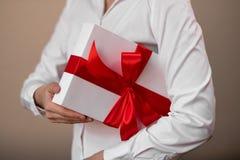 Μια γυναίκα σε ένα άσπρο πουκάμισο κρατά ένα δώρο Στοκ φωτογραφία με δικαίωμα ελεύθερης χρήσης