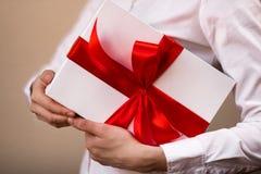 Μια γυναίκα σε ένα άσπρο πουκάμισο κρατά ένα δώρο underarm Στοκ Φωτογραφίες