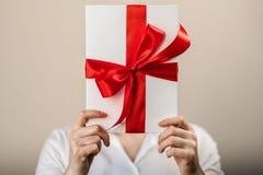Μια γυναίκα σε ένα άσπρο πουκάμισο κρατά ένα άσπρο κιβώτιο δώρων με ένα κόκκινο τόξο σατέν και κρύβει το κεφάλι της πίσω από ένα  Στοκ Εικόνες