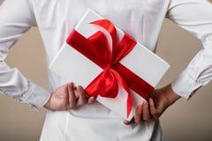 Μια γυναίκα σε ένα άσπρο πουκάμισο κρύβει ένα δώρο πίσω από την πίσω Στοκ Εικόνα