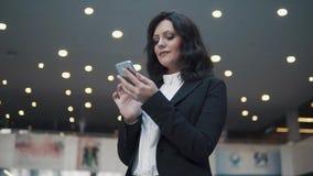 Μια γυναίκα σε ένα επιχειρησιακό κοστούμι περπατά μέσω του λόμπι ενός σύγχρονου κτιρίου γραφείων Η επιχειρησιακή γυναίκα χρησιμοπ απόθεμα βίντεο