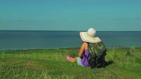 Μια γυναίκα σε ένα καπέλο αχύρου με ένα σακίδιο πλάτης πίσω από την πίσω κάθεται σε ένα βουνό και θαυμάζει τη φύση Πυροβολισμός α φιλμ μικρού μήκους