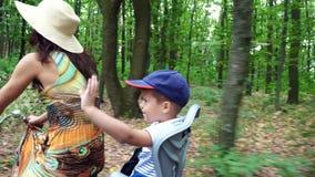 Μια γυναίκα σε ένα καπέλο και το φόρεμα, με ένα καλάθι των λουλουδιών, μαζί με το μικρό παιδί, οδηγούν το ποδήλατο, στο δάσος, απόθεμα βίντεο