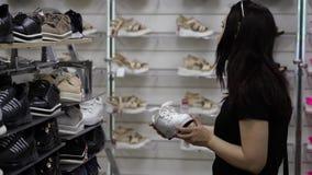 Μια γυναίκα σε ένα κατάστημα παπουτσιών, επιλέγει τα πάνινα παπούτσια Μια γυναίκα αγοράζει τα παπούτσια σε μια μπουτίκ απόθεμα βίντεο