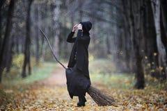 Μια γυναίκα σε ένα κοστούμι μαγισσών σε ένα δάσος στοκ φωτογραφίες