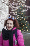 Μια γυναίκα σε ένα κόκκινο σακάκι σε ένα υπόβαθρο των ανθίζοντας κερασιών και του χριστουγεννιάτικου δέντρου Στοκ εικόνα με δικαίωμα ελεύθερης χρήσης