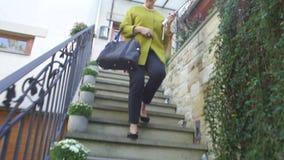 Μια γυναίκα σε ένα παλτό βγαίνει από το σπίτι, πηγαίνει κάτω από τα σκαλοπάτια απόθεμα βίντεο