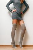 Μια γυναίκα σε ένα πουλόβερ και τις γυναικείες κάλτσες Στοκ Εικόνα