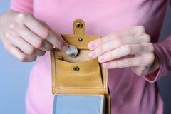 Μια γυναίκα σε ένα ρόδινο πουλόβερ βάζει ένα νόμισμα σε ένα ανοικτό πορτοφόλι Στοκ Εικόνες